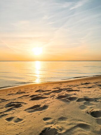 Dawn on the beach by the sea. Quiet calm water with small waves. Reflection of the sun on the water. Clear sky with clouds and footprints in the sand. Perfect morning