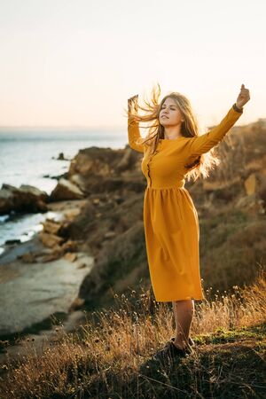 Calm young woman stands on the edge of a cliff in a yellow dress with her hands up and enjoys wind and the beauty of nature. The sun shines in the back. Back light. The joy of life. Balance. Calm Standard-Bild