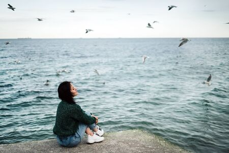 A young girl sits on a pier by the sea in windy weather and reflects on life. Seagulls fly over the water. Loneliness. Calmness and peace. Charge of inspiration. Sea breeze