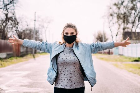 A young woman in a black medical mask in a turquoise jacket and a gray T-shirt with blond hair is standing holding his hands up on the road in the village. Looks at the camera. Quarantine concept.