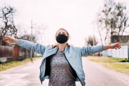 A young woman in a black medical mask with blond hair in a turquoise jacket and a gray T-shirt is standing holding her hands up on the road in the village, looking up. Quarantine concept. Virus.