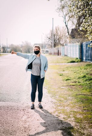 A young woman in a black medical mask in a turquoise jacket and a gray T-shirt stands on the road in the village with a raised hand and catches the car. Photo on the street. Quarantine concept.