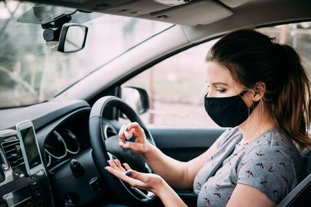 A young woman in medical mask with blond hair in a gray T-shirt is sitting in a car with right-hand drive and disinfects her hands with an antiseptic. Portrait photo. Quarantine concept. Standard-Bild
