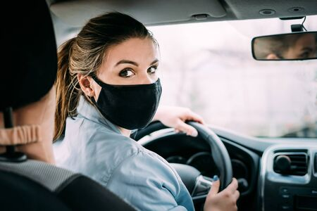 A young woman with blond hair in a black medical mask and a turquoise jacket is driving a left-hand drive. Portrait photo. Looks at the camera. Quarantine. Pandemic. Coronavirus concept.