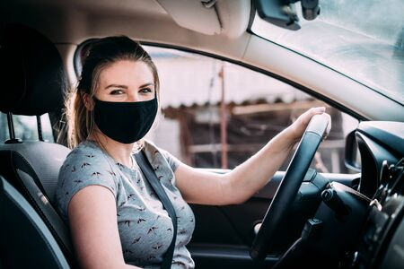A young woman in a black medical mask in a gray T-shirt with blond hair is sitting in a left-hand drive car. Her hands are on the steering wheel. Looks at the camera. Portrait photo. Quarantine. Standard-Bild