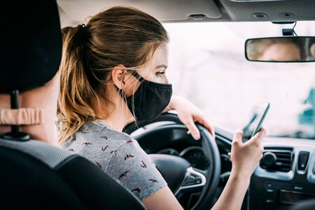 A young woman with blond hair in a black medical mask and a gray T-shirt is sitting in a car with left-handed control Covid-19. Quarantine concept.
