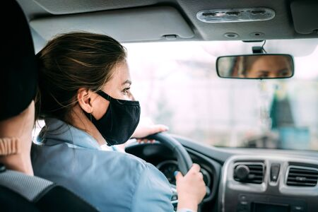 A young taxi driver woman in a black medical mask with blond hair and a turquoise jacket is driving a right-hand drive car. A woman looking at road. Masks protective. Quarantine. Virus. Pandemic.