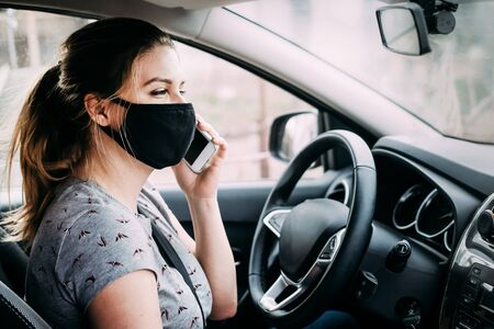 Young woman in a black medical mask with blond hair in a gray T-shirt sitting in a left-hand drive car and talking on the phone. Portrait photo. Quarantine concept. Virus. Pandemic. Coronavirus.
