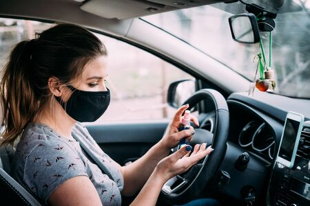 A young woman with blond hair in a black medical mask and a gray T-shirt is sitting in a car with left-handed control and sanitizes her hands with an antiseptic. Covid-19. Quarantine concept.