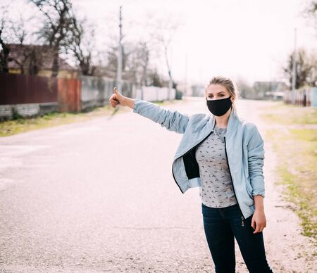 A young woman in a black medical mask in a turquoise jacket and a gray T-shirt stands on the road with a raised hand in the street in the village and catches a car. Quarantine concept. Virus. Standard-Bild