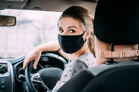 A young woman in a black medical mask and blond hair and a gray T-shirt is sitting at the wheel of a left-hand drive car. Portrait photo. Close up. Quarantine concept. Virus. Pandemic.