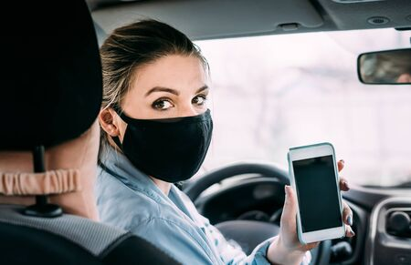 A young woman in a black medical mask in a birch jacket is sitting in a left-hand drive car and shows the phone screen to the camera. Looks at the camera. Portrait photo. Quarantine concept. Virus.