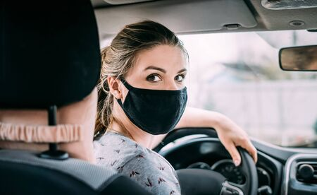 A young woman in a black medical mask with white hair and a gray T-shirt is sitting in a left-hand drive car. Looks at the camera. Portrait photo. Quarantine concept. Virus. Pandemic. Coronavirus.