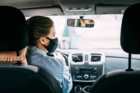 A young taxi driver woman in a black medical mask with blond hair and a turquoise jacket is driving a left-hand drive car. A woman looking at road. Masks protective. Quarantine. Virus. Pandemic.