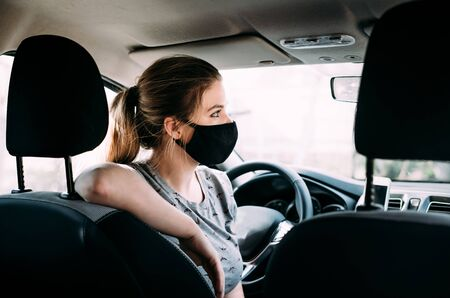 A young woman in a black medical mask with blond hair in a gray T-shirt is sitting in a left-hand drive car, put her hand on the seat. Portrait photo. Quarantine concept. Virus. Pandemic. Coronavirus