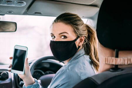 A young woman in a black medical mask in a birch jacket and blond hair shows her phone and sits in a car with right-hand drive. Looks at the camera. Portrait photo. Quarantine concept. Virus. Standard-Bild