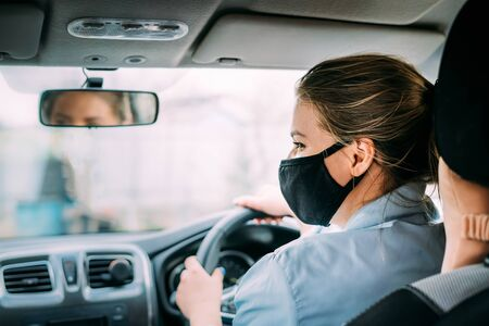 A young woman taxi driver in a black medical mask with blond hair in a jacket rides a right-hand drive car. Woman do not look at camera. Stay home concept. Quarantine. Virus. Coronavirus. Pandemic. Standard-Bild