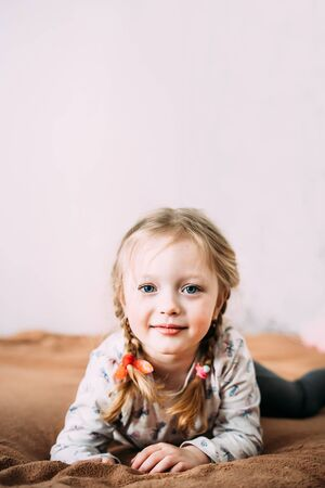 A smiling little girl with blond hair lies on the bed at home and looks at the camera. The background is light and blurry.