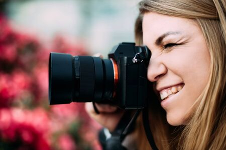 Young cute girl photographer holds a camera near the face photographing people on a floral blurred background and smiling. Work as a photographer