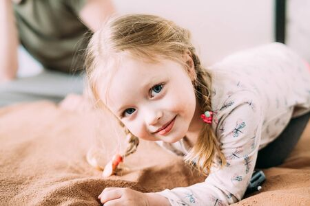 A smiling little child with blond hair lies on the bed on the blanket at home and looks at the camera. The background is light and blurry.