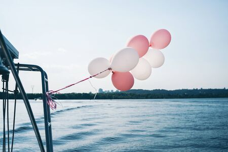 white and pink balloons on the yacht on the river with trees and blue sky buildings