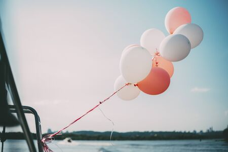 white and pink balloons on the yacht on the river with trees and blue sky Standard-Bild