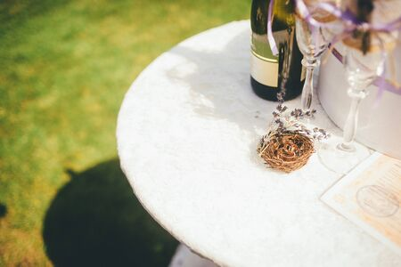 Wedding rings in a little decorative nest with a sprig of lavander on the white, round table. Close up, outoor wedding conception. Standard-Bild