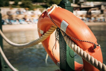 Close-up of a life buoy hanging on a fence near the sea on the beach. Sandy beach and sun loungers blurred in the background