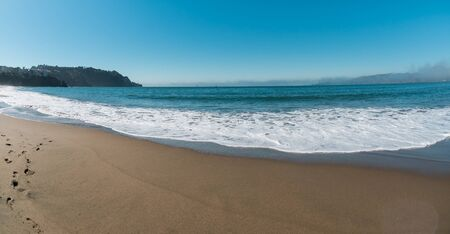 Gorgeous very beautiful panorama scenery of the ocean coast with blue water and clear light sand. Footprints in the sand. The houses stand on a hill in the background. No people. Sunny clear day