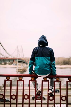 a young sports man sits on a handrail and looks at a river and a bridge in a blue green jacket, sweatpants and sneakers