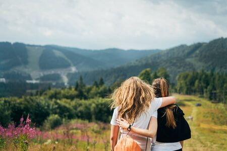 Two young girlfriends are standing on a mountain, hugging and enjoying nature with a backpack on flowering slopes on a warm sunny day.