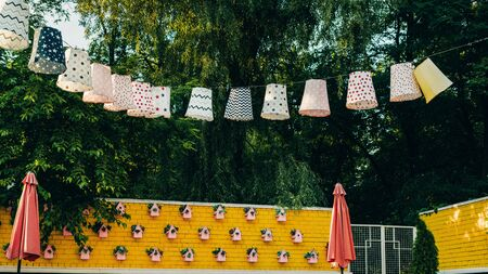 Close-up of paper cardboard holiday decorations hanging over a yellow brick wall in a forest. Pink birdhouses on the wall. Standard-Bild