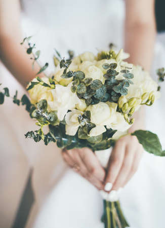Close-up of a delicate beautiful wedding bouquet in the hands of the bride in a white dress.