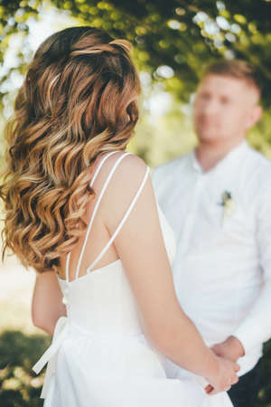A beautiful young bride in a white wedding dress stands and looks at her groom. Standard-Bild
