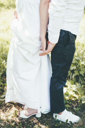 A couple of bride and groom stand in the park back to back and holding hands.