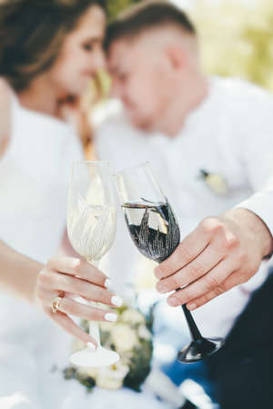 Close-up of a glass in a black and white rim in the hands on a wedding day.
