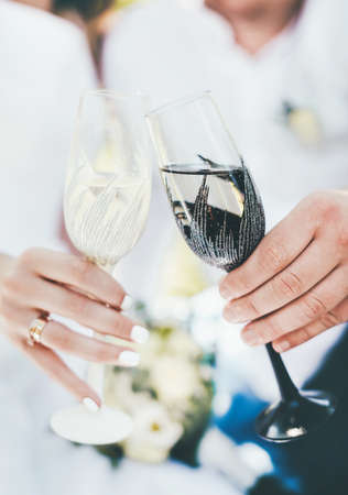 Close up of a glass in a black and white rim in the hands of the bride and groom on a wedding day. Standard-Bild