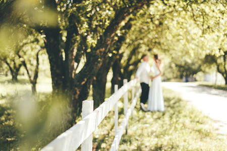 A close-up of a white wooden fence in the park and the newlyweds are standing near the fence