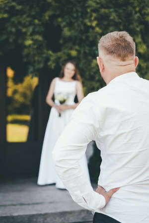 close-up the groom in a white shirt stands with his back and looks at his bride in a blurred dress.