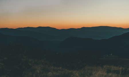 Beautiful orange sunrise in the mountains. Mountain ranges, fog.