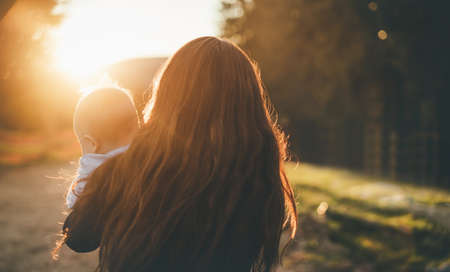 Blurred mom with child stands on the mountain at sunset. Standard-Bild