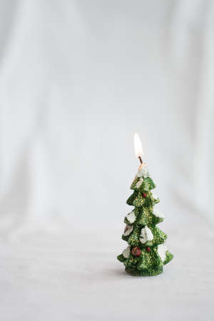 Christmas tree figurine candle burn on white background. Standard-Bild