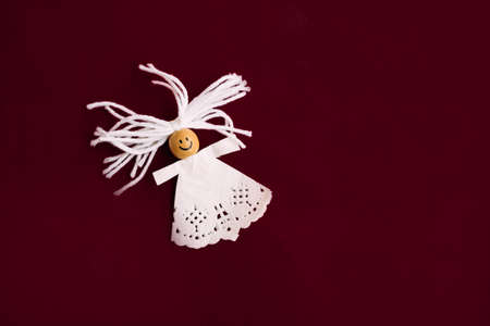 A paper figurine of an angel lies on a dark red background.