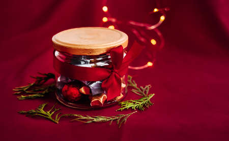 A decorative Christmas present jar with a golden lid and red small candies