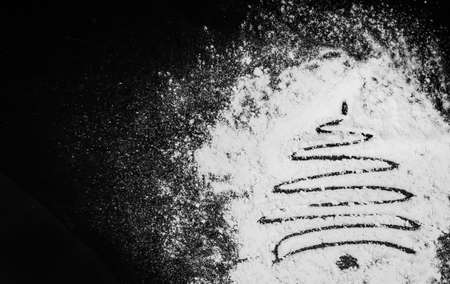 Blurred Christmas tree made of flour on a black background. Black and white photo. Standard-Bild