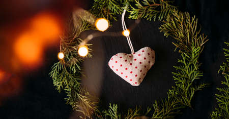 A soft focus knitted heart on a black textural background in a frame of Christmas tree branches with festive light bokeh. Standard-Bild