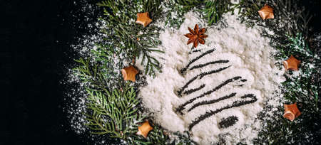 Blur shape of a Christmas tree of flour on a black background in a round frame of pine branches with small stars.