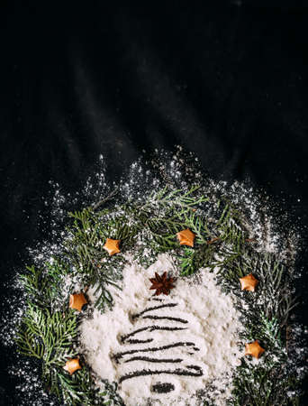 Blurred figure of a Christmas tree made of flour on a black background in a frame made of fir branches