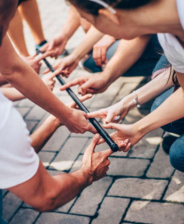 Vertical team building is an exercise for people with common interests in the company. Close-up of hands holding one stick