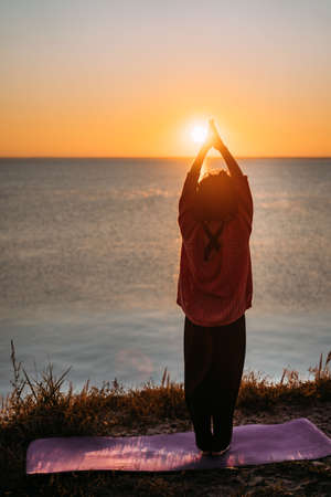 Vertical photo of a woman doing yoga at sunrise. Stands on a rug with raised joined hands. Looks at the water and the reflection of the sun in the water. Calmness, balance, calmness, meditation Standard-Bild